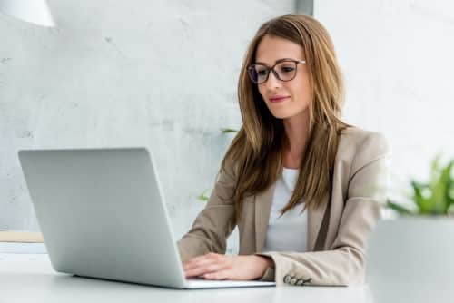 Eine Frau lächelnd am Schreibtisch in Anzug, die am Laptop arbeitet-