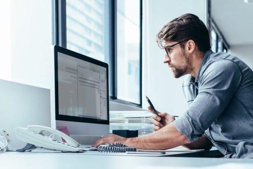 Ein Mann am Schreibtisch mit einem Stift in der Hand, der konzentriert den Bildschirm anschaut.