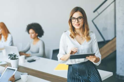 Eine Frau die sich lässig an einen Tisch lehnt und ein Tablet in der Hand hält, im Hintergrund sind andere Personen am Tisch am arbeiten.