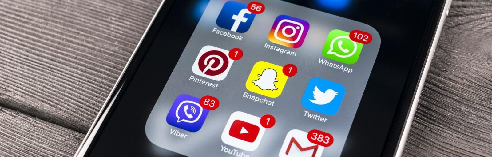 Eine Nahaufname eines Handys im Menü mit diversen Social Media App Icons, die zu sehen sind.