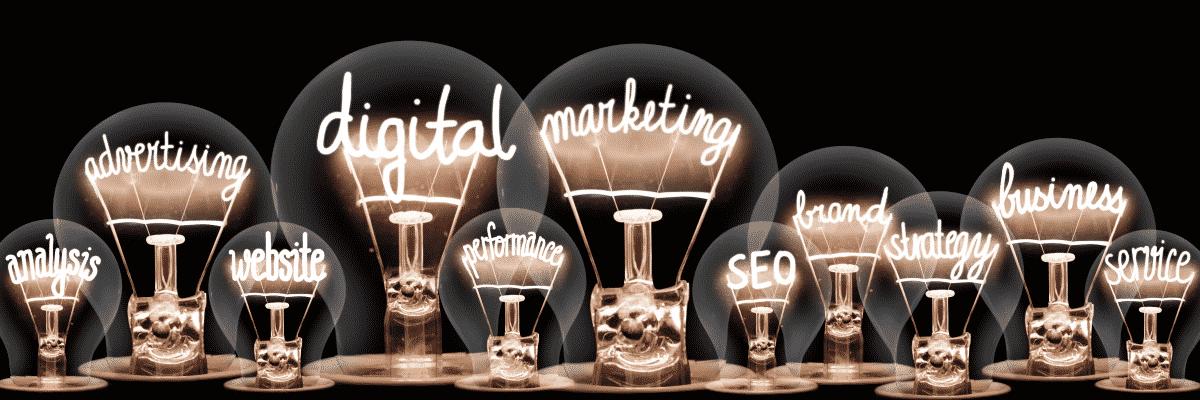 Viele verschiedene Glühbirnen auf einem Tisch auf denen in Neon alles zum Thema Marketing steht.