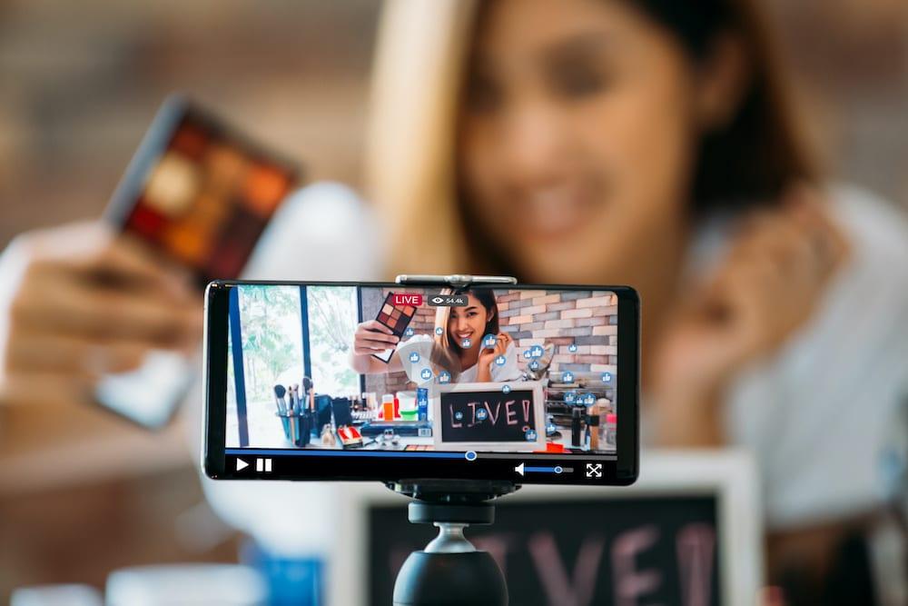 Ein Ausschnitt von einem Video auf dem Handy wie eine Frau live ist und sich mit der Handykamera filmt, rechts ein Icon mit Infos zum webinar.